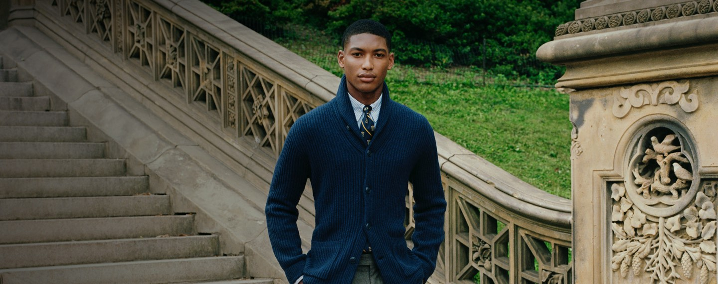 Man in navy shawl cardigan layered with shirt & tie