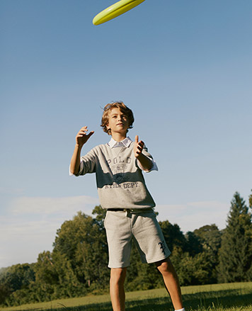 Boy wears light grey sweatshirt and sweat shorts.