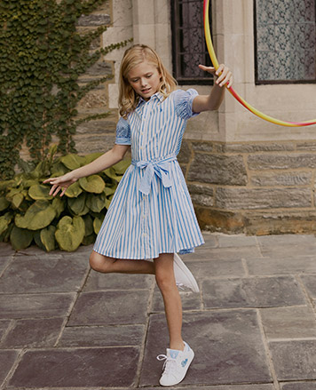 Girl wears blue-and-white striped cotton shirtdress.