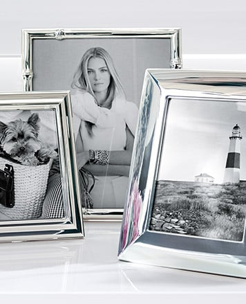 Three silver picture frames on white table