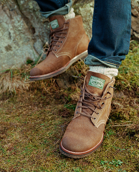 Worn brown leather low-top boots with laces
