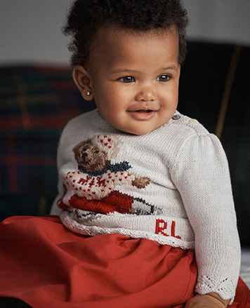Baby girl wears white ice-skating Polo Bear sweater.