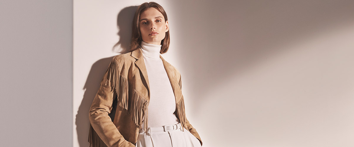Woman in tan fringe jacket & off-white turtleneck & trousers